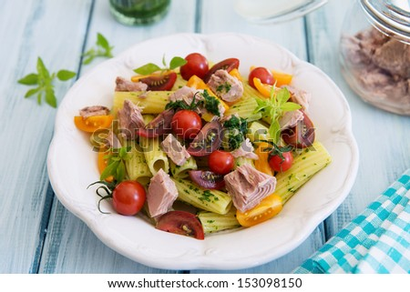 Pasta with tuna, fresh herbs, mixed tomatoes and pesto on the beautiful old planks  - stock photo