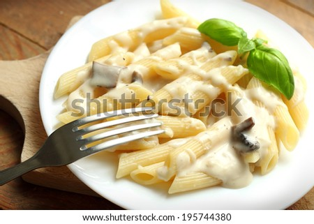 Pasta with white mushroom sauce in a plate placed on the table