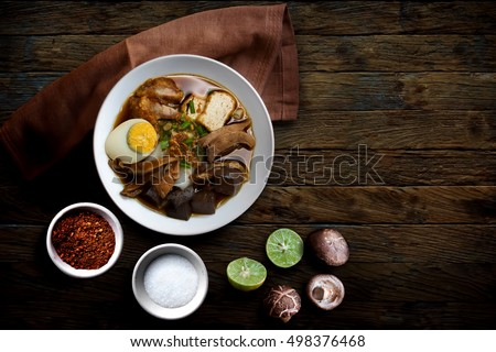 Paste of rice flour with pork, Chinese roll noodle soup over wooden table.