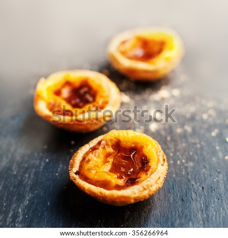 Pasteis de nata, typical Portuguese egg tart over dark background