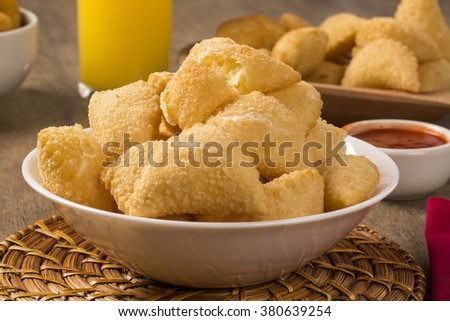 Pastel, a Brazilian snack, with a bar in the background. Cheese pastry on wooden background. - stock photo
