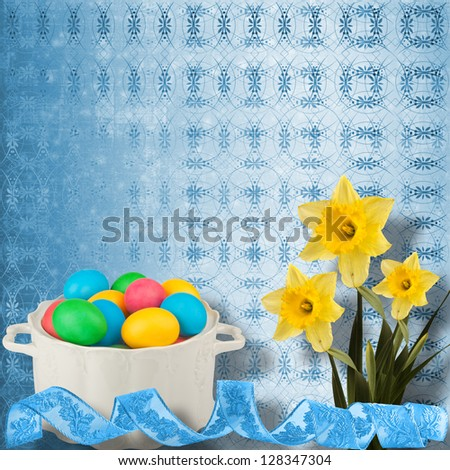 Pastel background with colored eggs and narcissus to celebrate Easter