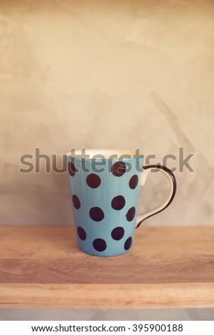 Pastel blue cup with dot on wooden background and cement wall. - stock photo