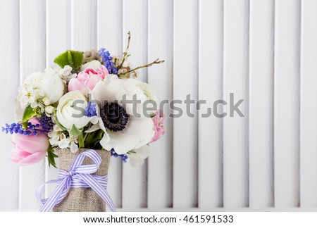 Pastel bouquet from pink tulips, violet grape hyacinths, white anemones, violet veronica and white buttercup with violet ribbon with white wooden shutter background