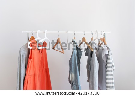 Pastel Color Female Clothes on Open Cloth Rail Wooden Hanger Grey Wall - stock photo