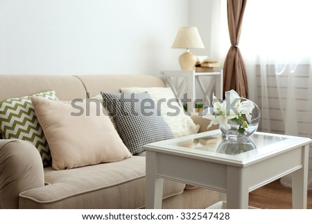 Pastel color sofa with beautiful pillows and vase with flowers on the table in front of it in the room - stock photo