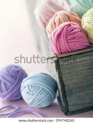 Pastel color yarn balls in an old wooden basket