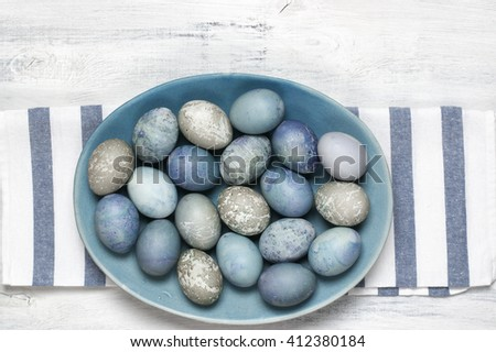 Pastel colored blue and grey Easter eggs in handmade ceramic dish with towel on rustic white wooden background. Top view point. - stock photo