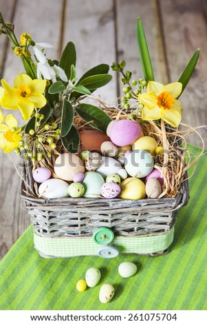 Pastel colored easter eggs in gray wicker basket decorated with checkered ribbon, hay and spring flowers on green striped cloth over grunge style wooden table