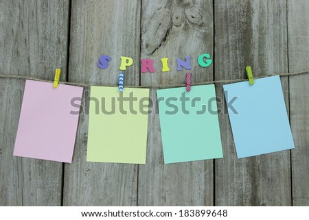 Pastel colored note cards hanging on clothesline with wooden background