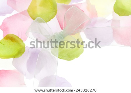 Pastel colored silk floral petals and bow on white background for Easter & spring themes. - stock photo