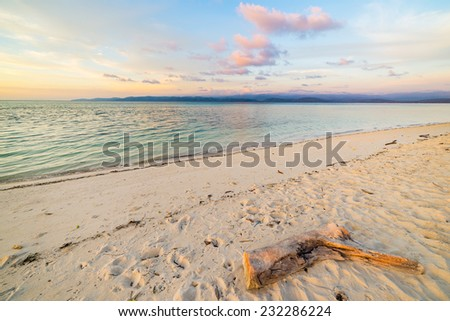 Pastel colored sky, clouds and seascape at dusk. Wide angle view from a white sandy beach with trunk fragment in the foreground. Tanjun Karang, Central Sulawesi, Indonesia. - stock photo