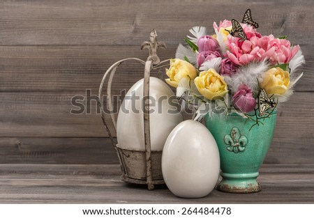 Pastel colored tulip flowers with vintage easter eggs decoration. Retro style toned picture. - stock photo