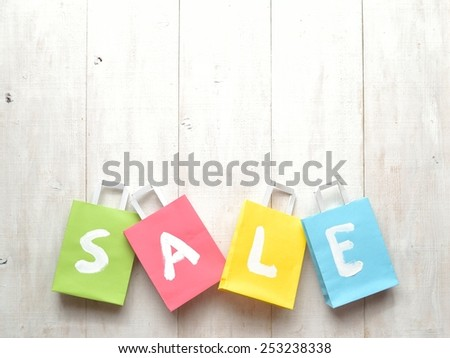 Pastel colors bargain sale shopping bags on white wooden background - stock photo