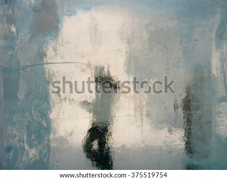 Pastel colors silhouette of a women taken through ice block - stock photo
