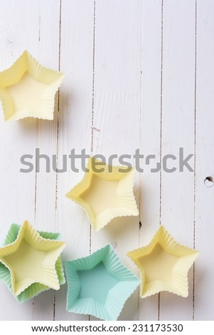 Pastel colors  silicone molds for muffins on background from white painted wooden planks. Selective focus. - stock photo