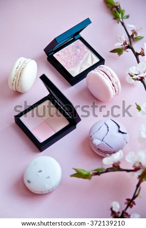 Pastel colour macaron and blush powders with peach blossom on a pink background