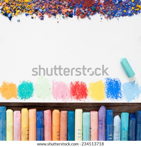 Pastel crayons and white paper sheet of sketchbook with spots of paints and pigment dust.  - stock photo