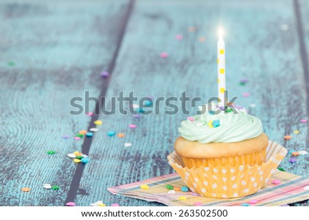 Pastel cupcake with a candle on green wooden vintage background