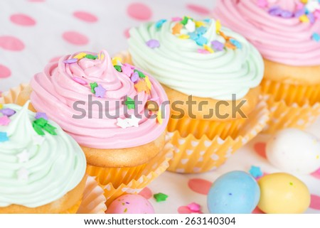 Pastel Easter cupcakes with candy and sprinkles, shallow depth of field - stock photo