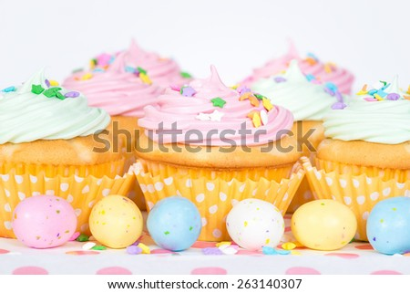 Pastel Easter cupcakes with candy and sprinkles, shallow depth of field