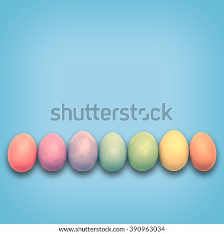 Pastel Easter eggs aligned, blue background - stock photo