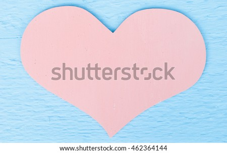 pastel pink heart on a blue wood background with space for text