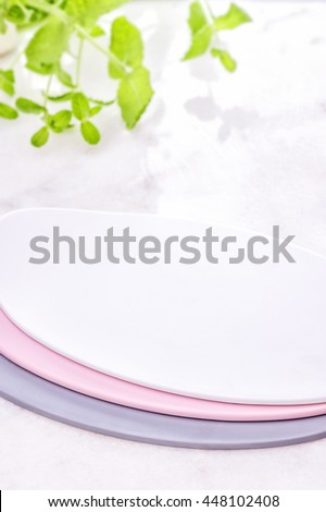 Pastel plates on white shine table on a fresh mint background. Tableware set. Dishes for a meal. Empty template to put your food on the plate. picnic - stock photo