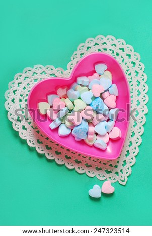 pastel powder sugar candies in heart shaped pink box on green background