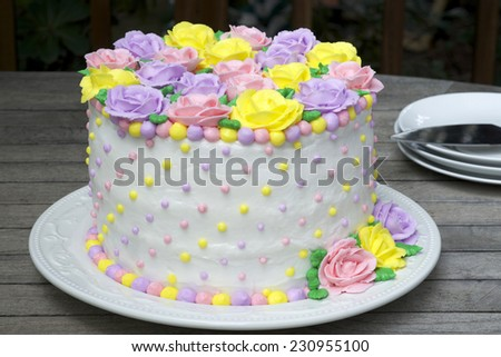 Pastel Rainbow Yellow, Pink, Purple butter cream frosting handmade roses on a round cake frosted with white icing and embellished with yellow, pink and purple dots of buttercream frosting.  - stock photo