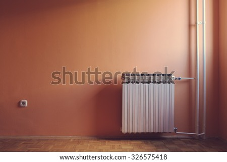 Pastel retro color of warm windows natural illuminated empty room with water central heating radiator and power outlet.  - stock photo