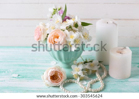 Pastel sweet roses and jasmine flowers  in vase, candles  on turquoise wooden background. Selective focus.