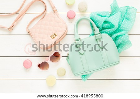 Pastel theme mood board with fashion accessories (bags, sunglasses, scarf) for girls. White rustic wooden background. Flat lay composition (from above, top view). - stock photo