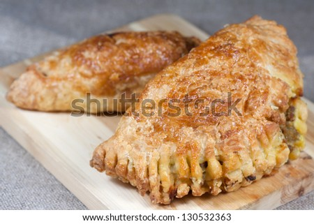 pasties filled with minced meat on a wooden board with beige background