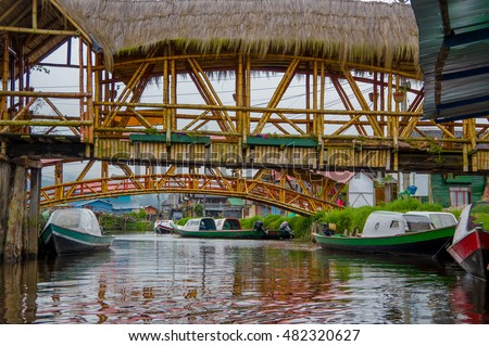 PASTO, COLOMBIA - JULY 3, 2016: some wood bridges standing over some boats on a river close to la cocha lake