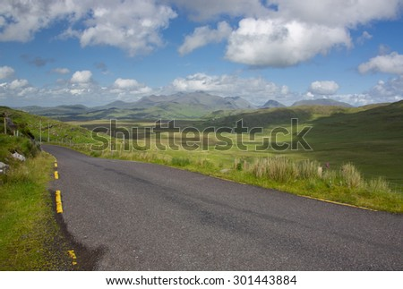 Pastoral landscape showing road and fields Ring of Kerry on west coast of Ireland near the mountains on a sunny day with green fields and blue skies with clouds and mountains.