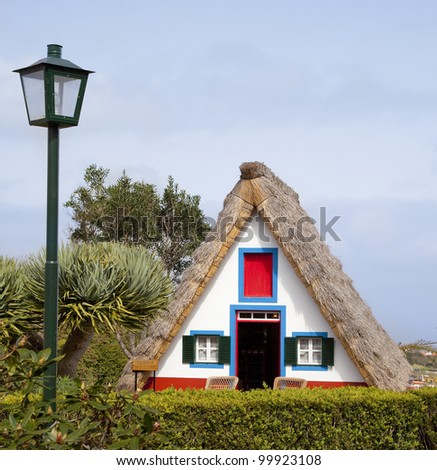 Pastoral landscape. Small rural house with a triangular thatched roof. The red door and small windows with shutters. Santana city, Madeira island, Portugal - stock photo