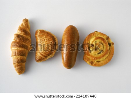 Pastries: croissant, apple turnover, bun, and raisin danish - stock photo
