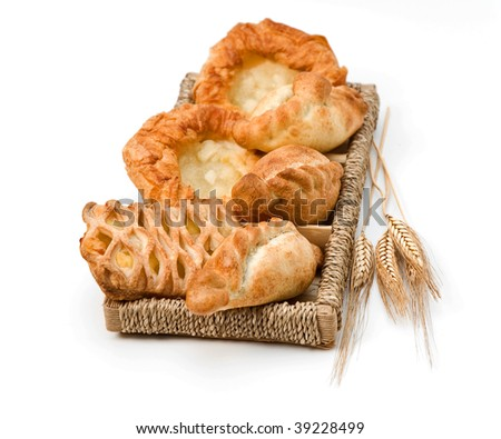 Pastries on a wooden tray and wheat ears