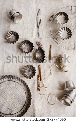 Pastries vintage concept. The tart pan and tartlets props on a rustic napkin table with flour and aromatic spices. Top view. - stock photo