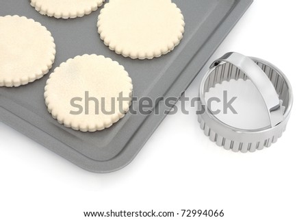 Pastry biscuit dough on a baking tray with cookie cutter, over white background.