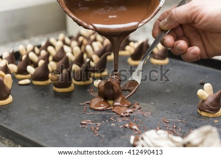 pastry chef covering the biscuits with melted chocolate