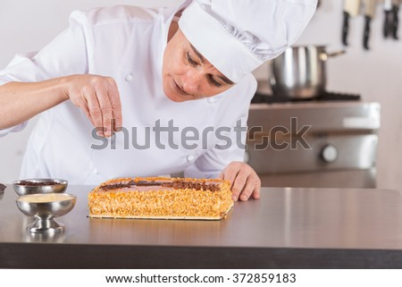 Pastry chef decorating cake yolk and cream