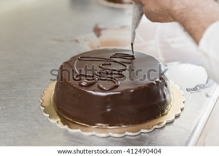 pastry chef garnish a cake with melted chocolate - stock photo
