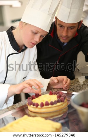 Pastry cook teaching student to make a cake - stock photo