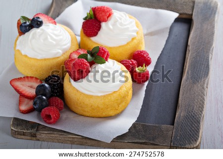 Pastry cups filled with whipped cream and fresh berries - stock photo