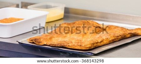 Pastry eclairs decorated with black and white chocolate and orange rind.eclairs, pastries, baking - stock photo