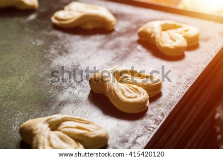 Pastry on baking tray. Heart-shaped baked goods. Delicious and lovely. Quality dough and traditional recipe. - stock photo