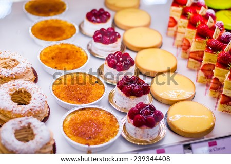 Pastry shop with variety of donuts, Creme brulee, cakes with fruits and berries - stock photo