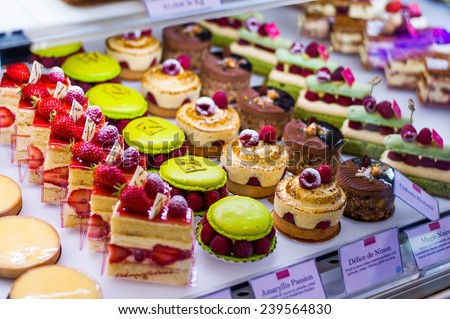 Pastry shop with variety of donuts, muffins, creme brulee, cakes with fruits and berries - stock photo